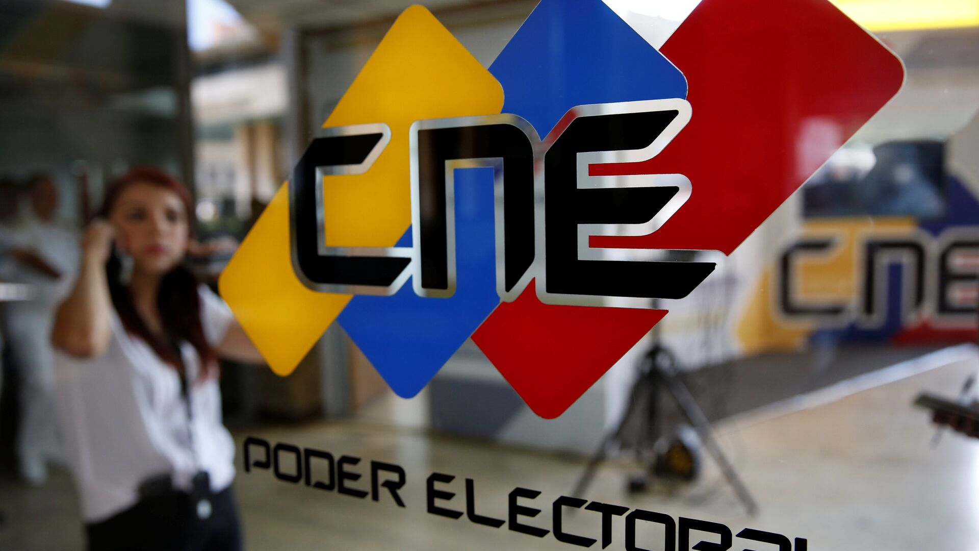 People walk past a logo of the National Electoral Council (CNE) at its headquarters in Caracas - Sputnik Mundo, 1920, 06.09.2021