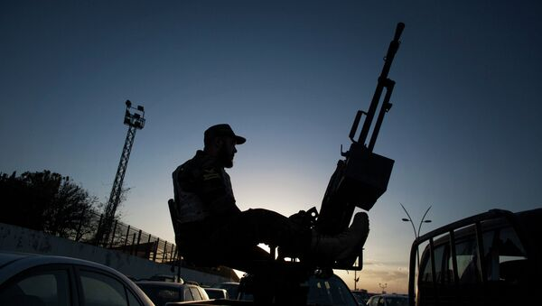 A Libyan army soldier stands guard sitting on an antiaircraft truck during the handover of the Nawaseen military compound, which was the headquarters of Libyan militias, in Souk al-Juma district, Tripoli, Libya - Sputnik Mundo