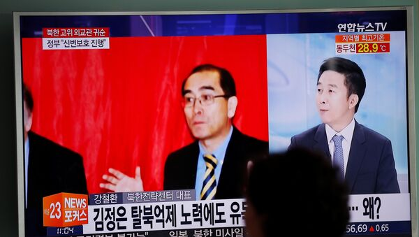 A passengers walks past a TV broadcasting a news report on Thae Yong Ho, North Korea's deputy ambassador in London, who has defected with his family to South Korea, at a railway station in Seoul - Sputnik Mundo
