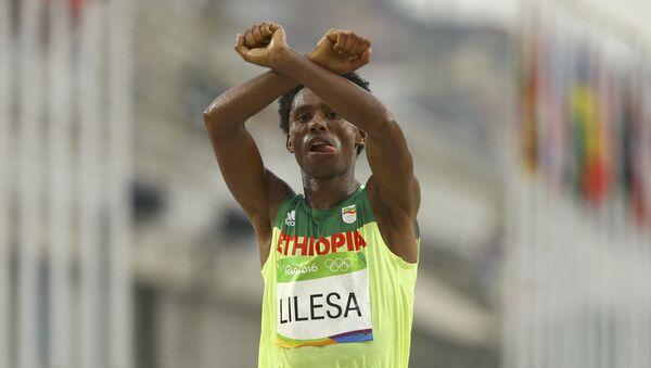 Lilesa cruzando la meta y haciendo un gesto como si tuviera los brazos esposados, en señal de protesta contra la persecución del Gobierno etíope contra la etnia oromo - Sputnik Mundo
