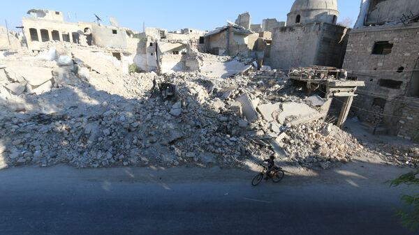 A boy rides a bicycle near rubble of damaged buildings in the rebel held al-Maadi district of Aleppo, Syria, August 31, 2016 - Sputnik Mundo