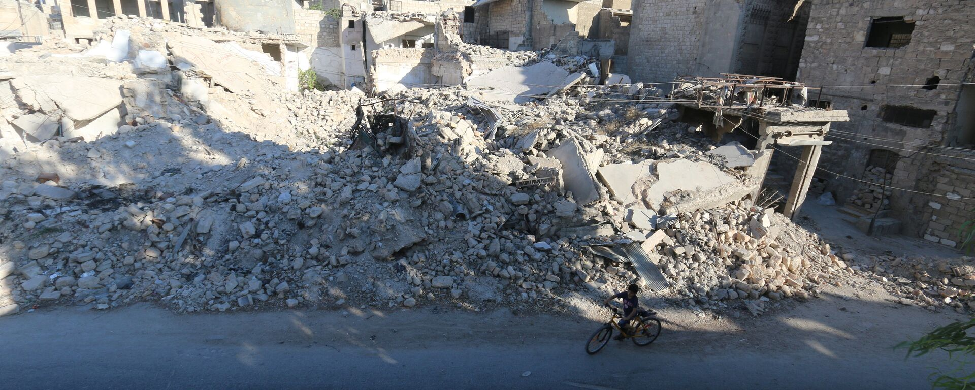 A boy rides a bicycle near rubble of damaged buildings in the rebel held al-Maadi district of Aleppo, Syria, August 31, 2016 - Sputnik Mundo, 1920, 01.06.2021