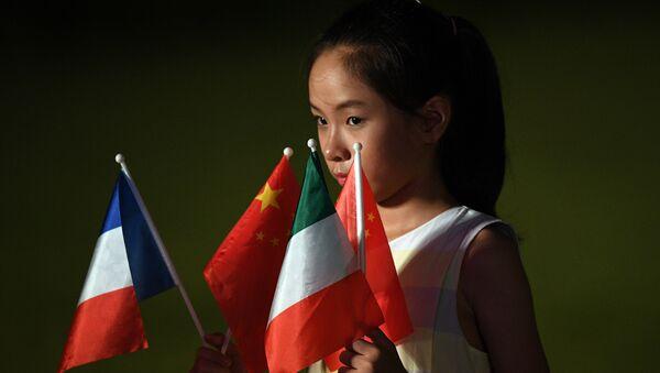Una niña sostiene las banderas de los países miembros del G20 en la cumbre en Hangzhou - Sputnik Mundo