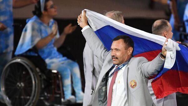 Un miembro de la selección paralímpica bielorrusa lleva la bandera de Rusia durante la ceremonia de inaugaración de los Juegos Paralímpicos de 2016 en Río de Janeiro - Sputnik Mundo