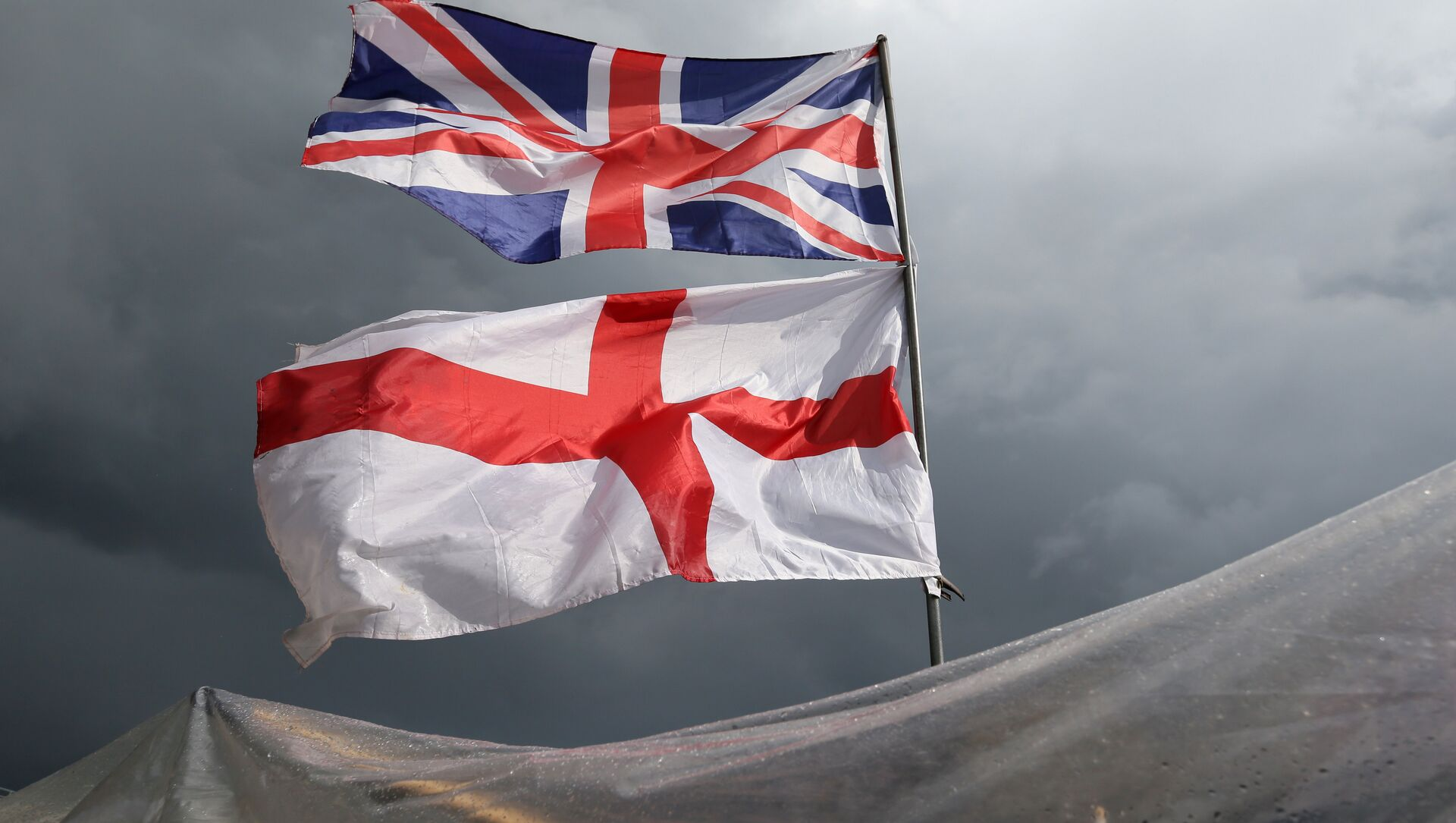 The flag of the United Kingdom of Great Britain and Northern Ireland, top, and the flag of England fly above a souvenir stand on Westminster Bridge following yesterday's EU referendum result, London, Saturday, June 25, 2016. Britain voted to leave the European Union after a bitterly divisive referendum campaign. - Sputnik Mundo, 1920, 09.02.2021