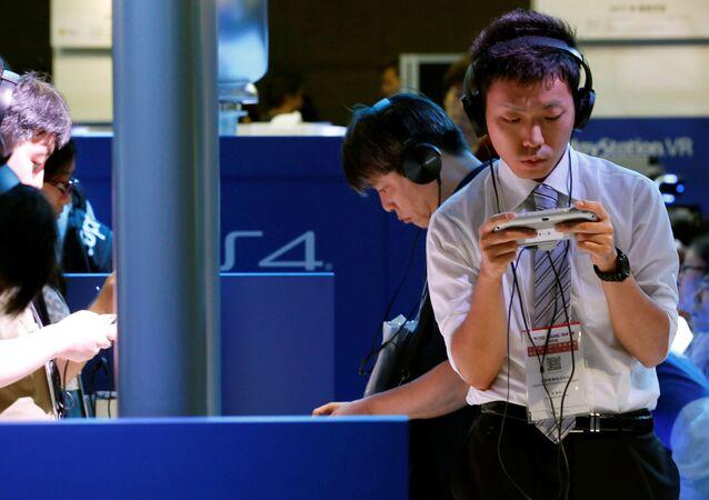 Посетители выставки Tokyo Game Show 2016 играют в Sony's PlayStation Vita, Токио, Япония