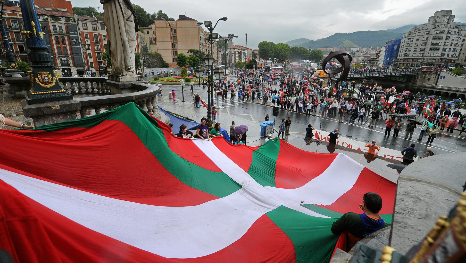 Pro independence demonstrators hold a big Ikurrina (Basque flag) at the entrance of the northern Spanish Basque city of Bilbao's Town Hall as they protest in favour of the Basque flag (Ikurrina) - Sputnik Mundo, 1920, 28.01.2021