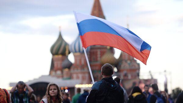Un hombre con la bandera de Rusia en la Plaza Roja de Moscú - Sputnik Mundo