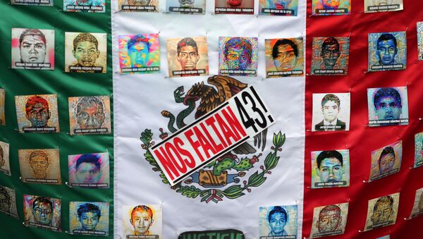 A Mexican flag and some pictures of the 43 missing students is seen in a march to demand justice for the 43 missing students of Ayotzinapa College Raul Isidro Burgos to mark the two-year anniversary of their disappearance in the state of Guerrero, in Mexico City, Mexico, September 26, 2016. - Sputnik Mundo
