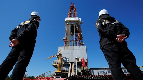 Workers look at a drilling rig at a well pad of the Rosneft-owned Prirazlomnoye oil field outside the West Siberian city of Nefteyugansk, Russia, August 4, 2016 - Sputnik Mundo