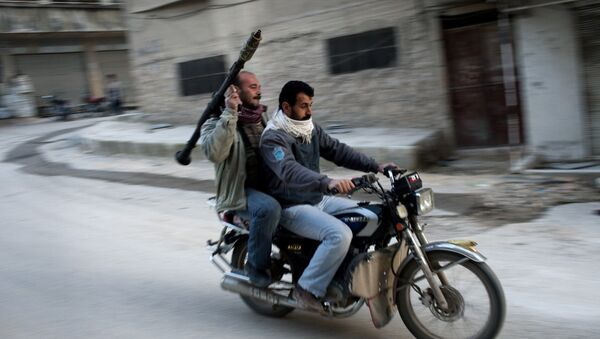 Supporters of the Free Syrian Army ride a motorcycle with a rocket-propelled grenade in Kafar Taharim, Syria. - Sputnik Mundo