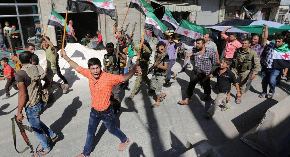Militantes rebeldes y ciudadanos sirios con las banderas de la oposicón durante una protesta
