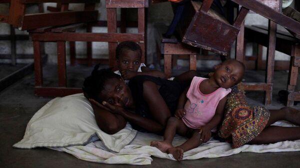 Mujer con dos niños en un refugio por el huracán Matthew en Haití - Sputnik Mundo