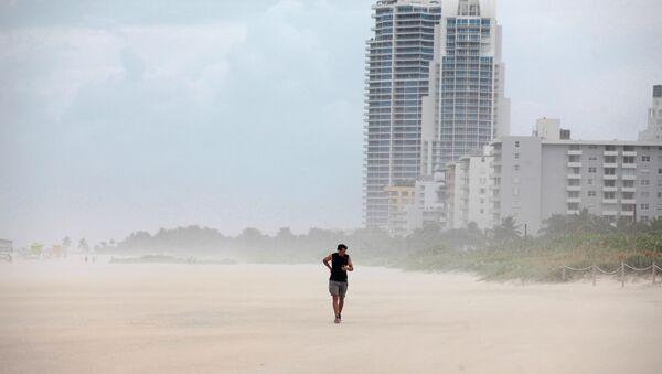 Una persona camina por la playa antes de la llegada del huracán Matthew en Miami Beach - Sputnik Mundo