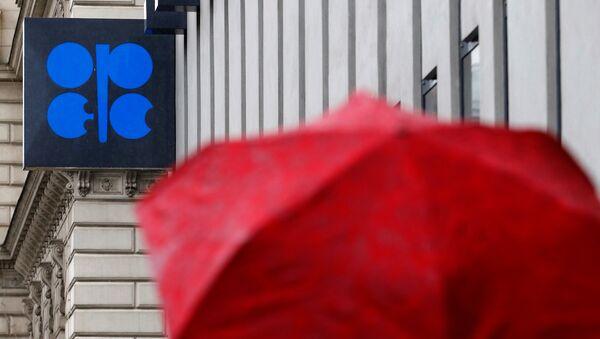 A person carrying an umbrella walks by the OPEC headquarters in Vienna - Sputnik Mundo
