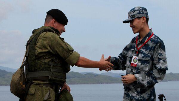 Un soldado ruso y un soldado chino durante las maniobras ruso-chinas en Vladisvostok (archivo) - Sputnik Mundo