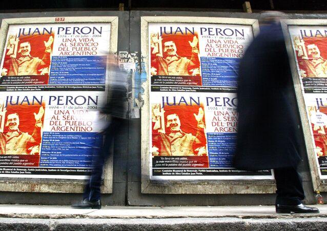 Las personas pasan por las carteles de Juan Domingo Perón