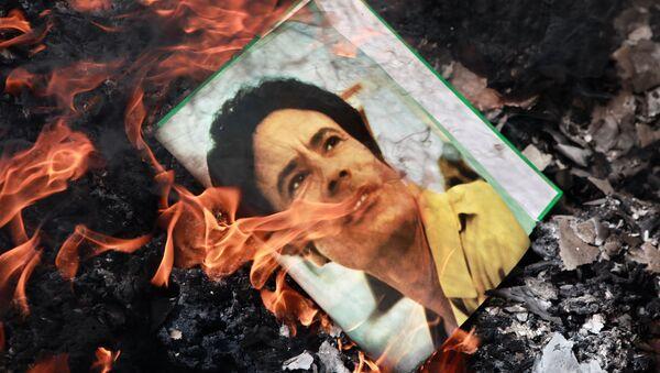 El retrato de Muamar Gadafi, quemado en la calle de Benghazi, Libia, en 2011 - Sputnik Mundo