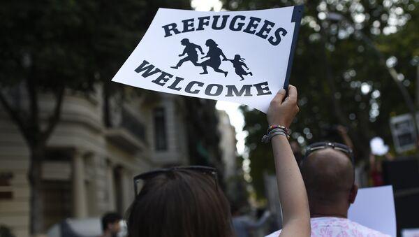 Mujer sostiene cartel de bienvenida a refugiados - Sputnik Mundo