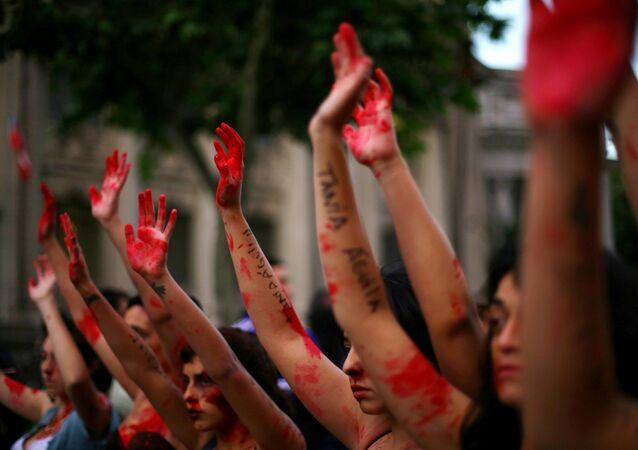 Los manifestantes alzan sus manos pintadas en una marcha pacífica contra la violencia de género en Santiago, Chile.