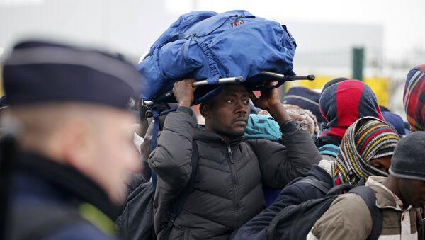 Un migrante espera la evacuación de campamento de Calais - Sputnik Mundo