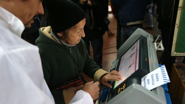 Una anciana argentina usando una máquina de voto electrónico (archivo) - Sputnik Mundo