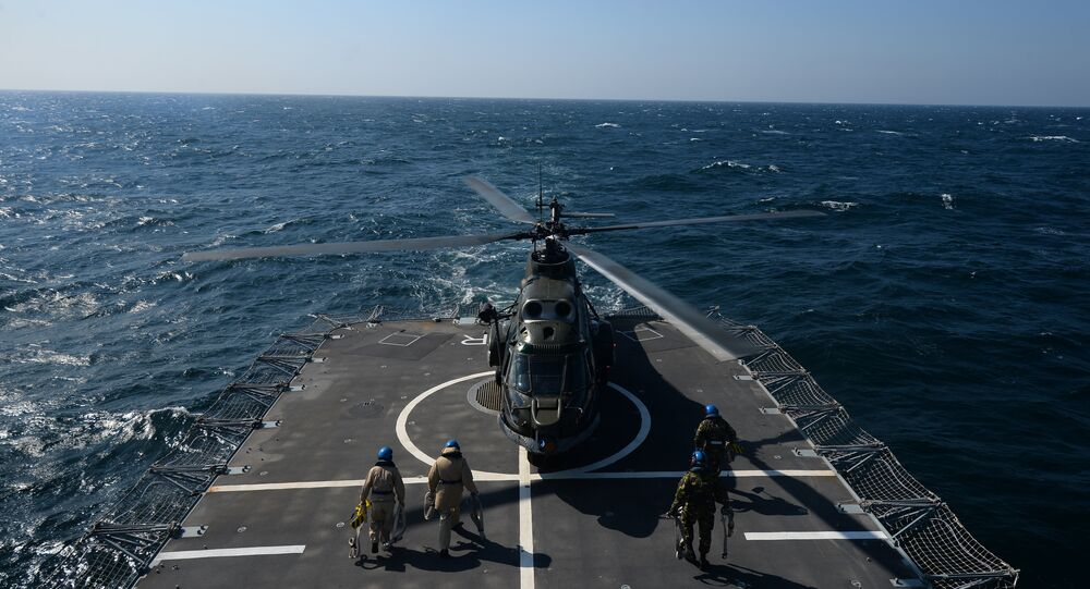 Romanian frigate Regina Maria personnel with the NATO Standing Maritime Group-2 maintain a helicoper which just landed on the heliport of the ship during a military drill on the Black Sea, 60km from Constanta city March 16, 2015