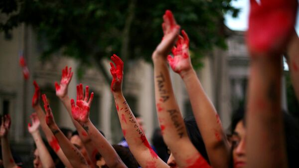 Demonstrators rise their painted hands during a peaceful march against gender violence in Santiago, Chile - Sputnik Mundo