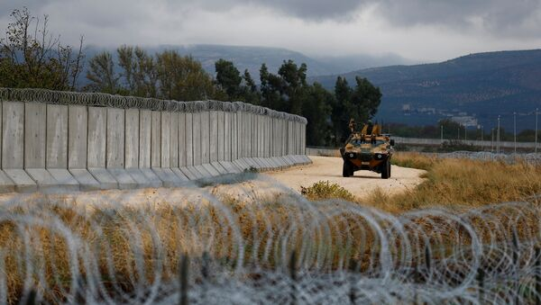 An armoured military vehicle drives past a wall along the border between Turkey and Syria, near the southeastern village of Besarslan, in Hatay province, Turkey, November 1, 2016 - Sputnik Mundo
