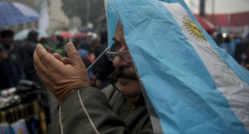 A man covered with an Argentinian flag takes part in a demonstration takes part in a demonstration of Argentine Central Workers (CTA) in front of Casa Rosada at Plaza de Mayo square, against President Mauricio Macri and economy measures in Buenos Aires on June 2, 2016.