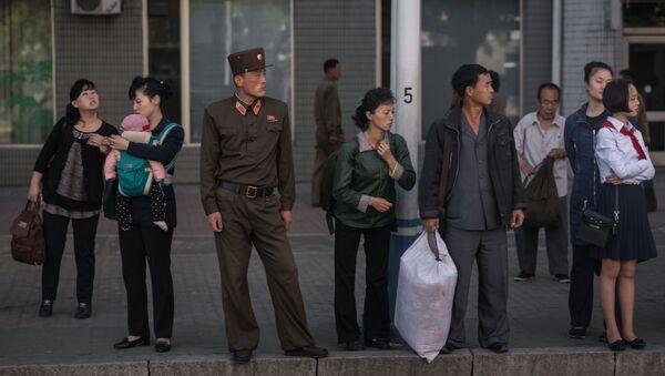 La gente esperando el autobús en una parada de Pyongyang, Corea del Norte - Sputnik Mundo