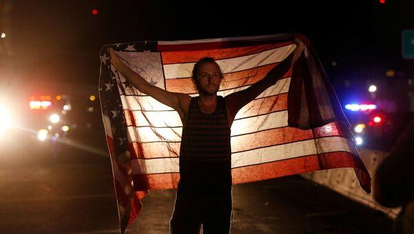 Un manifestante con la bandera de EEUU durante protestas tras la victoria de Donald Trump - Sputnik Mundo
