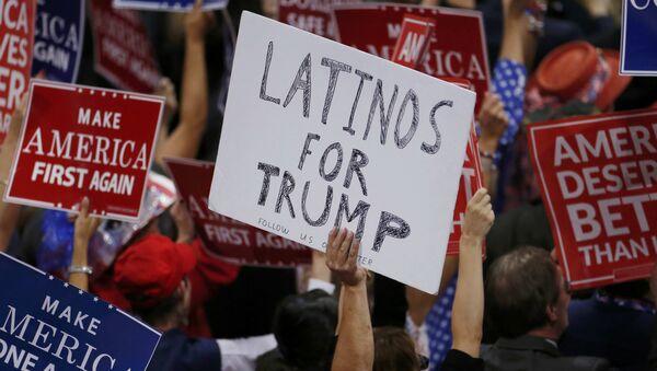 Un partidario de Donald Trump con una carpeta Latinos a favor de Trump en una reunión - Sputnik Mundo