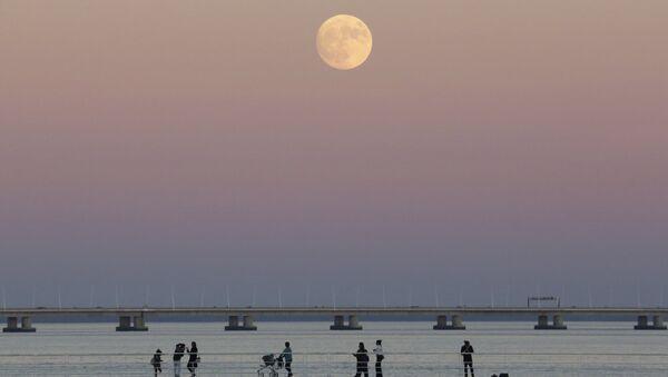 People stroll along the Tagus riverside in Lisbon as the moon rises Sunday, Nov. 13 2016 - Sputnik Mundo