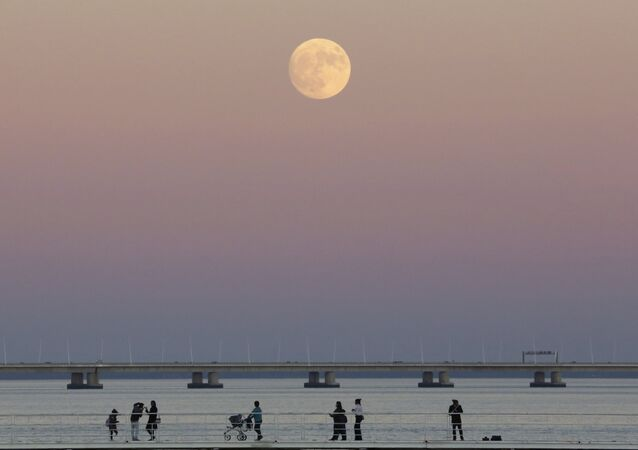 People stroll along the Tagus riverside in Lisbon as the moon rises Sunday, Nov. 13 2016