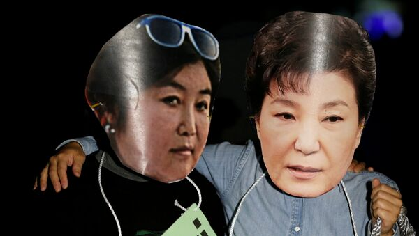 Manifestantes surcoreanos con las fotos de Choi Soon-sil, y la expresidenta del país, Park Geun-hye (archivo) - Sputnik Mundo