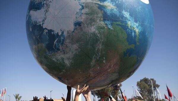 Members of International delegations play with a giant air globe ball outside the COP22 climate conference on November 18, 2016, - Sputnik Mundo