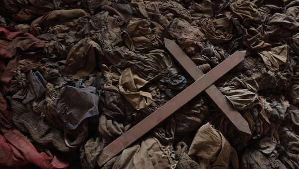 a wooden cross lies among clothes from some of the estimated 10,000 Tutsis killed in a two-day massacre at Nyamata church, now a memorial to the 1994 genocide, in the town of Nyamata, 30 kilometers outside Kigali, Rwanda. Callixte Mbarushimana is on Interpol's Wanted List for the crime of genocide in his native Rwanda where he is accused of having planned and executed the slaughter of his U.N. colleagues. Fifteen years on, he lives freely in France, as do dozens of other men accused of having plotted the murder of Rwanda's Tutsi minority. - Sputnik Mundo