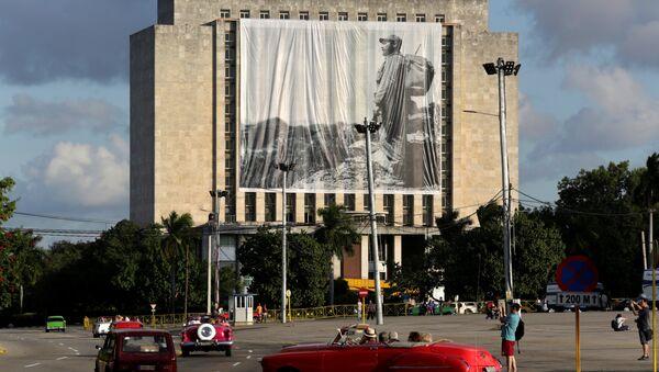 Fusil y mochila a la espalda en la Sierra Maestra, el líder histórico de la Revolución cubana, Fidel Castro, preside desde una gigantografía el homenaje póstumo de cubanos y extranjeros - Sputnik Mundo