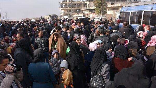 Syrians that evacuated the eastern districts of Aleppo gather to board buses, in a government held area in Aleppo, Syria in this handout picture provided by SANA on November - Sputnik Mundo
