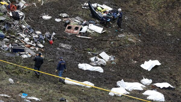 Rescue workers walk next to bodies from the wreckage of a plane that crashed into the Colombian jungle with the Brazilian soccer team Chapecoense onboard near Medellin, Colombia - Sputnik Mundo