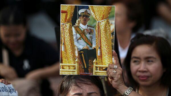Una mujer con el retrato del nuevo rey de Tailandia - Sputnik Mundo
