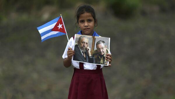 Niña sostiene retratos de los líderes cubanos - Sputnik Mundo