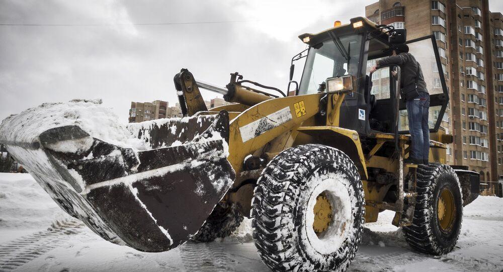 Un tractor de servicios públicos recoge la nieve en Moscú