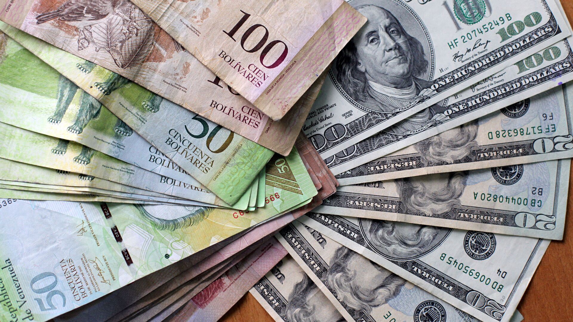 Picture of US dollars and Venezuelan Bolivares fuertes (2,15 per dollar) bills in Caracas on August 17, 2009. Venezuelan President Hugo Chavez's government will soon announce new measures to restore the currency balance which --according to Chavez-- is suffering from a distortion due to an unofficial, though legal, exchange market - Sputnik Mundo, 1920, 16.03.2021