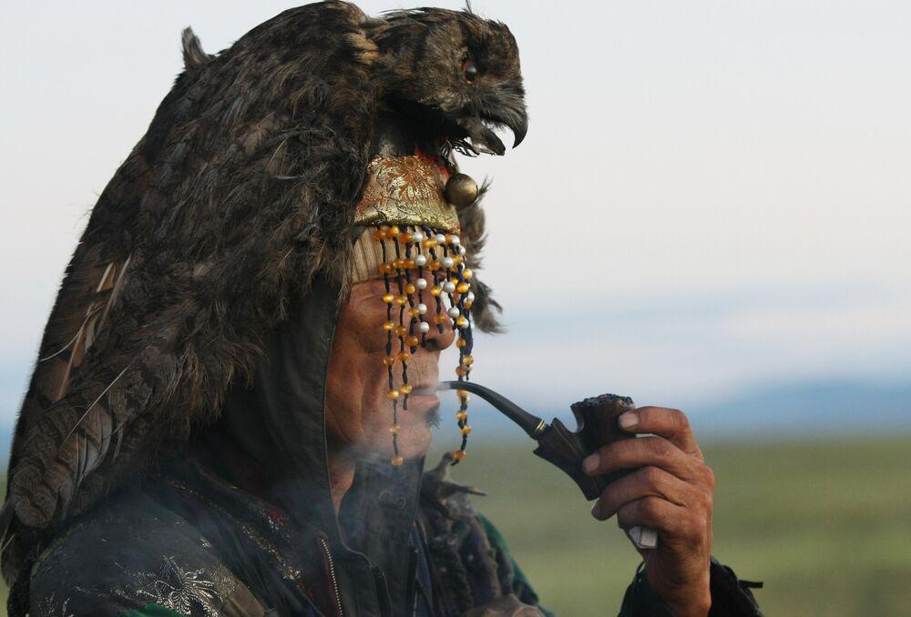 Chamán de la república de Tuvá, portando algunos de los elementos típicos de su profesión en esta región, espera el atardecer.