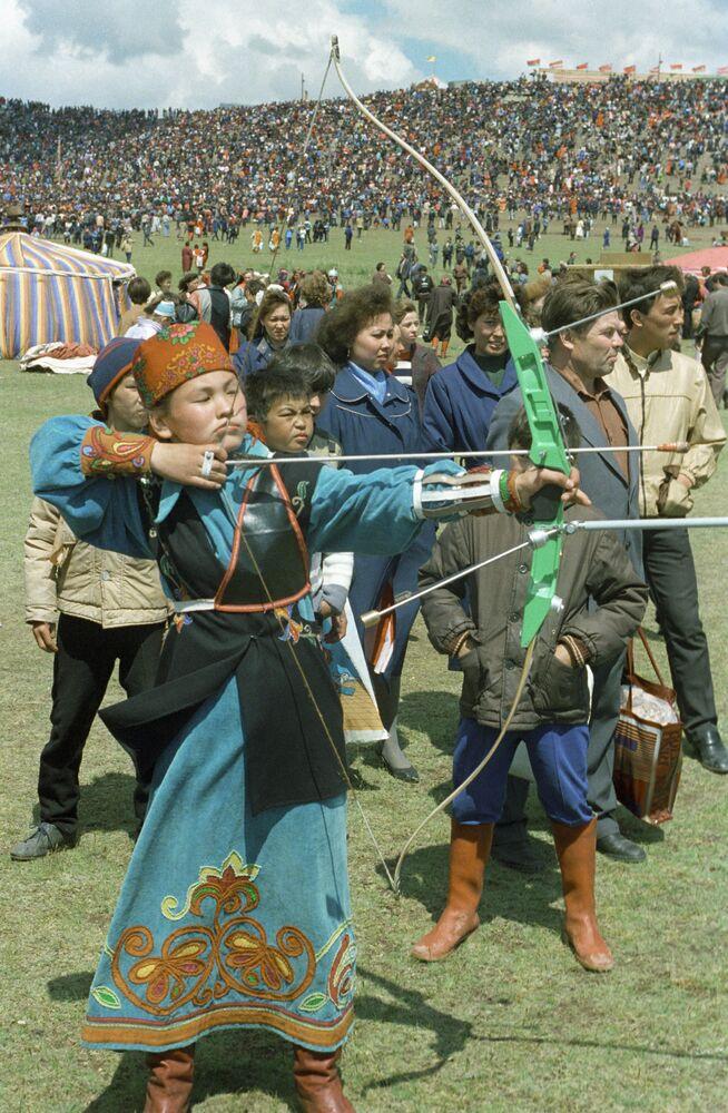 Joven de la república de Jakasia, ataviada con su traje nacional, dispara un arco.