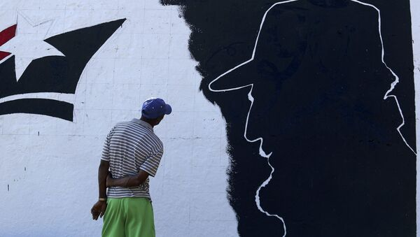 A man looks at a mural representing Cuba's late President Fidel Castro in the outskirts of Santiago de Cuba - Sputnik Mundo