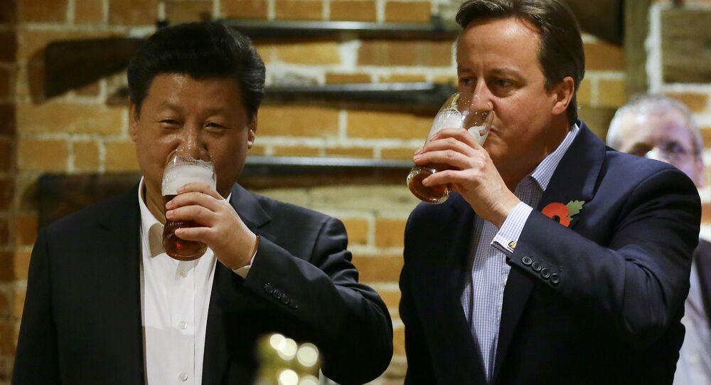 El presidente de China, Xi Jinping, y el primer ministro británico, David Cameron, toman una copa de cerveza