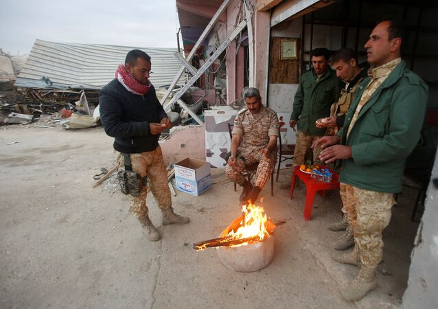 Peshmerga forces warm themselves by a fire in the town of Bashiqa, after it was recaptured from the Islamic State, east of Mosul,